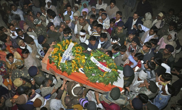 Mourners gather around the body of Indian Army soldier Lance Naik Hamraj who was allegedly killed by Pakistani soldiers on the line-of-control in Kashmir, during his funeral in Mathura district, Uttar Pradesh. (Photo: AP)