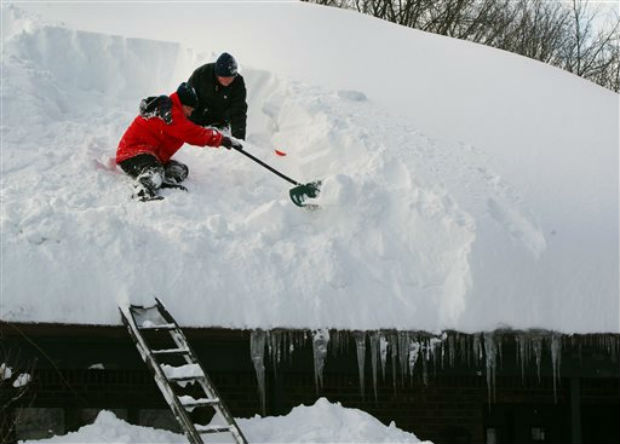 Beth Mack and her son Daniel clear the roof of their home in Eden, N.Y. Friday, Nov. 21, 2014. A snowfall that brought huge drifts and closed roads in the Buffalo area finally ended Friday, yet residents still couldn't breathe easy, as the looming