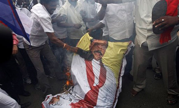Indian Tamil activists beat a burning effigy of Sri Lankan President Mahinda Rajapaksa during a protest against a Sri Lankan court verdict sentencing five Indian fishermen and three locals to death for smuggling narcotics, in Chennai, India, Friday