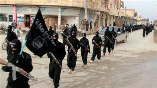 This undated file image posted on a militant website on Tuesday, Jan. 14, 2014, which has been verified and is consistent with other AP reporting, shows fighters from the al-Qaida linked Islamic State of Iraq and the Levant (ISIL) marching in Raqqa
