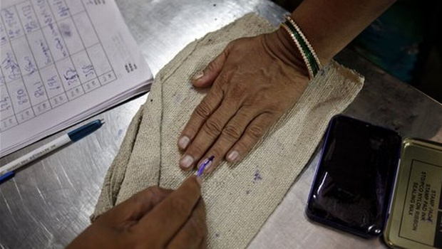 Polling officer applies ink on to a voter finger   Photo AP