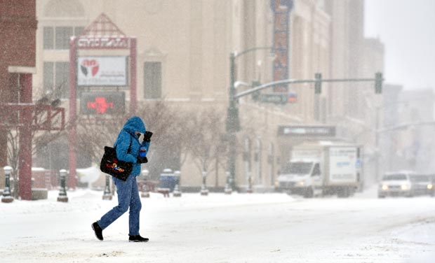 A pedestrian bundles up against the strong wind and cold as she crosses Main Street on High Street in downtown Elkhart, Indiana. (Photo: AP)
