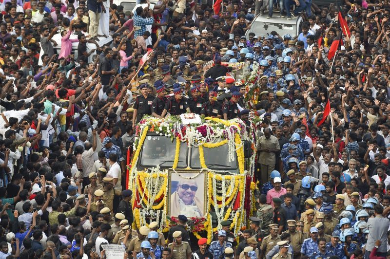 People gather to pay their last respects to DMK chief M Karunanidhi as his cortege passes through the streets of Chennai. (Photo: PTI)