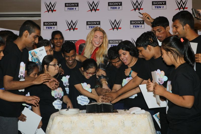 WWE Superstar Charlotte Flair cuts cake with the Special Olympics Bharat Athletes at the Children's Day celebration in Mumbai.