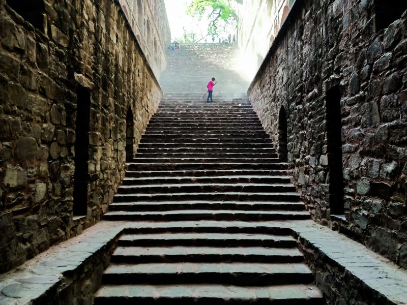 A man cleaning stairs of a stepwell