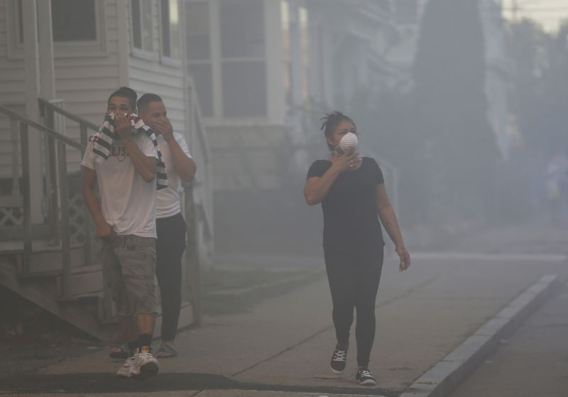 People cover their faces to protect themselves from heavy smoke from a fire on Bowdoin Street in Lawrence. (Photo: AP)
