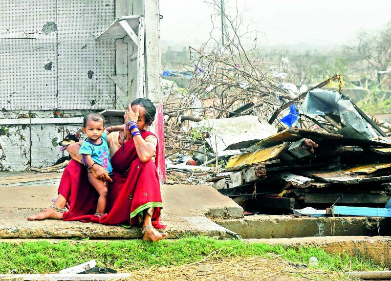 A woman sits with her child next to storm-damaged buildings in Puri, Odisha