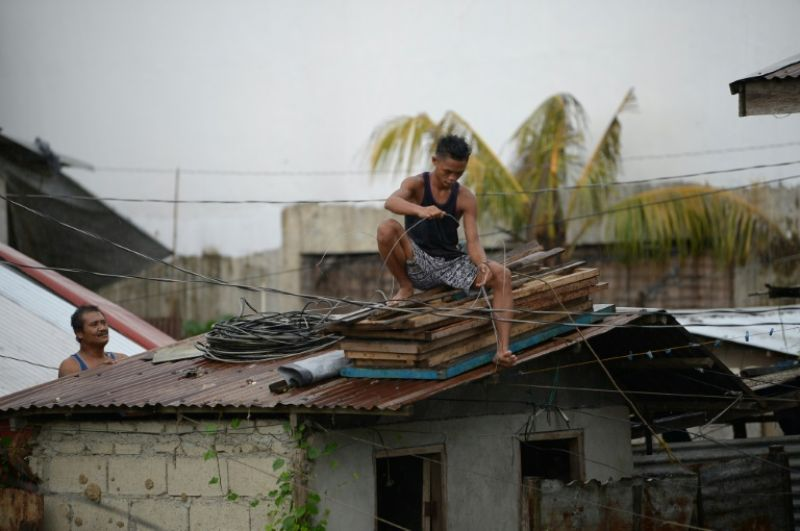 Residents secure the roof of their house as Typhoon Mangkhut approaches the Philippine city of Tuguegarao. (Photo: AFP)