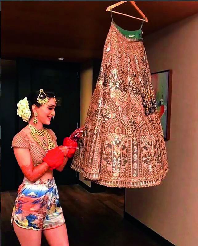 A bride posing with her lehenga in boxers