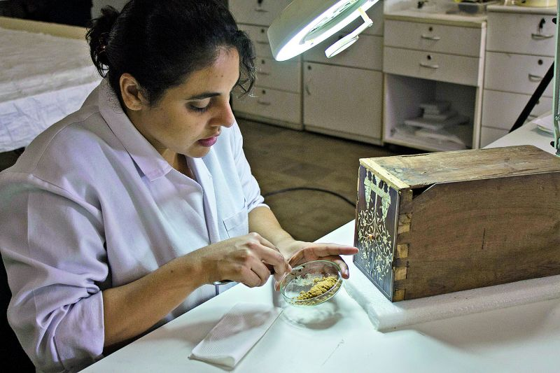Nivedita Dhage working on the wooden cabinet