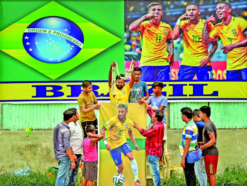 Fans from Kolkata offer a garland to a poster of Neymar. (Photo: PTI)