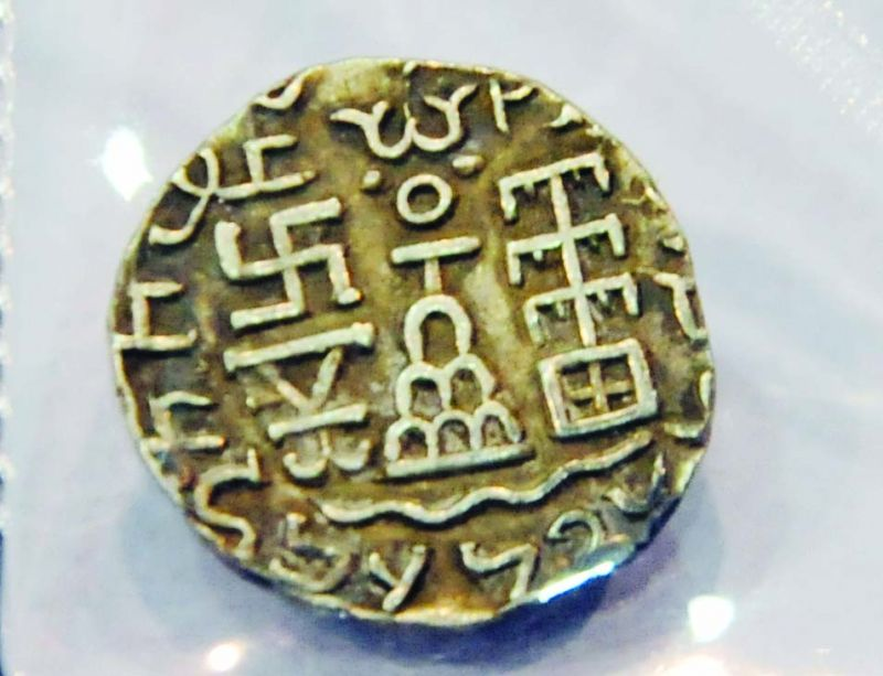 A silver coin with a Swastika motif.