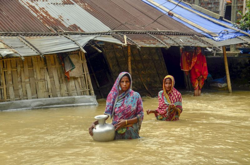 Villagers carry clean water as they wade across flood-affected areas at Nilambazar village, in Karimganj on Sunday. (Photo: PTI)