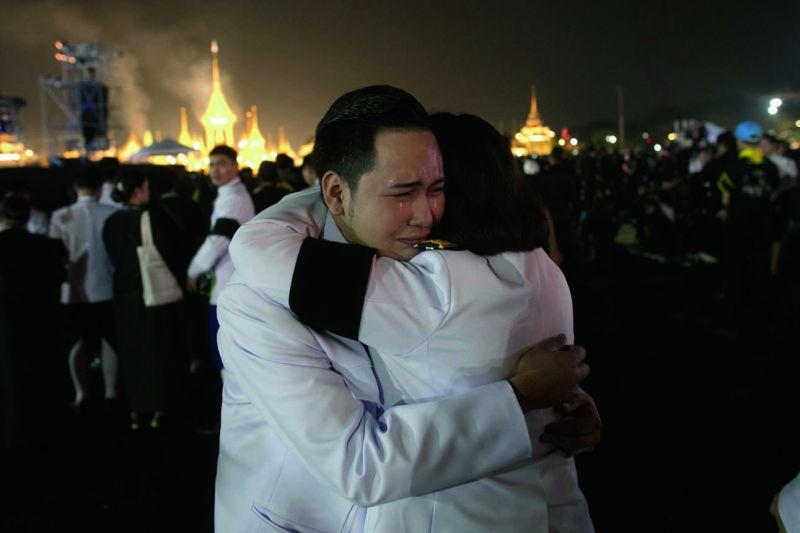 Thai officials hug as smoke rises from the royal crematorium of late King Bhumibol Adulyadej