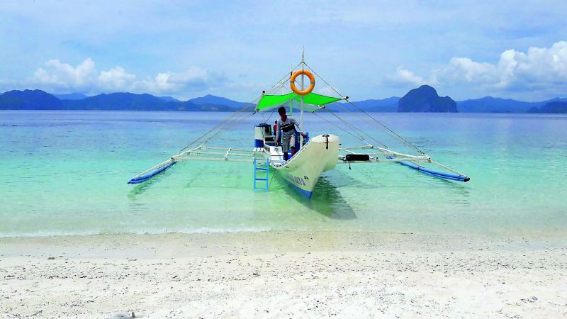 The boat that brings us to the crystal clear water and white sandy beaches of a private island in El Nido
