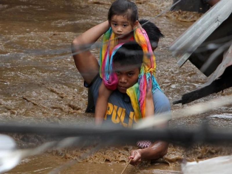 A policeman carries a young girl as he wades through a flooded street in Cagayan City after the Cagayan River swelled caused by heavy rains brought by Tropical Storm Tembin. (Photo: AFP)