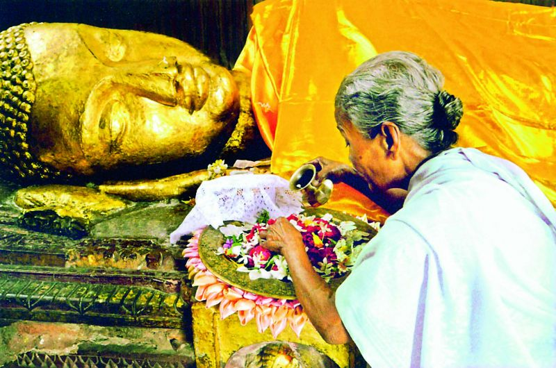 """A piligrim makes offerings in front of an ancient gilded structure of the dying Buddha in Kushinagar near the place where he died, probably in his eightieth year. His last words were reported as, """"Decay is inherent in all worldly things. Strive for your own liberation with diligence"""""""