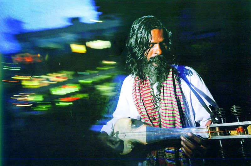 A Baul fakir sings on a rooftop above the light and noise of Bangladesh's capital Dhaka