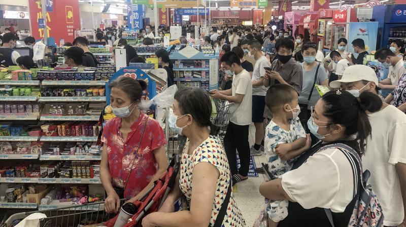 This photo taken on August 2, 2021 shows people buying items at a supermarket in Wuhan, in China's central Hubei province, as authorities said they would test its entire population for Covid-19 after the central Chinese city where the coronavirus emerged reported its first local infections in more than a year. (STR / AFP)