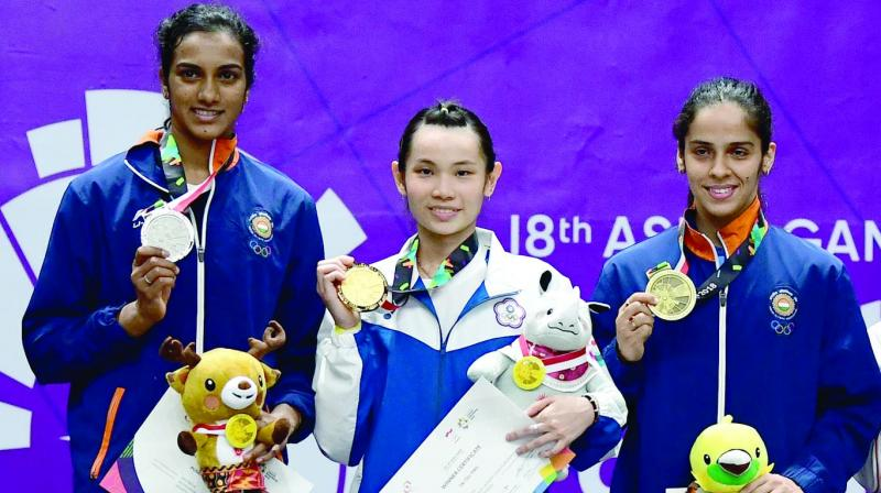 Silver medallist P.V. Sindhu (left), gold medallist Tai Tzu-Ying (centre) and bronze medallist Saina Nehwal pose during the awards ceremony for the women's singles badminton event in Jakarta. (Photo: AFP)