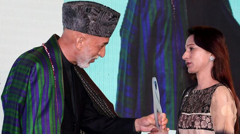 Former President of Afghanistan Hamid Karzai felicitates mother of Dhaka terror attack victim Faraaz Ayaaz Hossain with the mother Teresa memorial award in Mumbai. (Photo: PTI)
