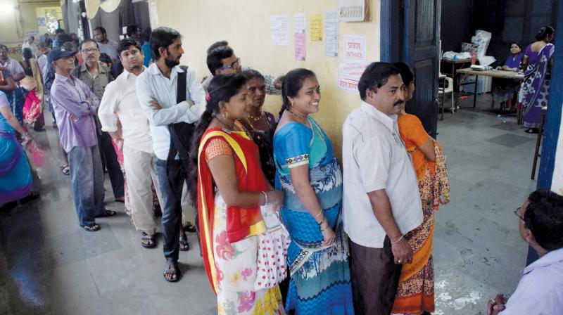 Voters stand in a queue outside a polling booth.