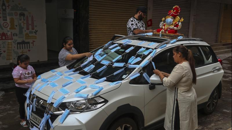 A family decorates their car with face masks prior to joining a procession for Ganesha immersion in the Hussain Sagar Lake on the final day of Ganesh Chaturthi festival in Hyderabad. (AP Photo)