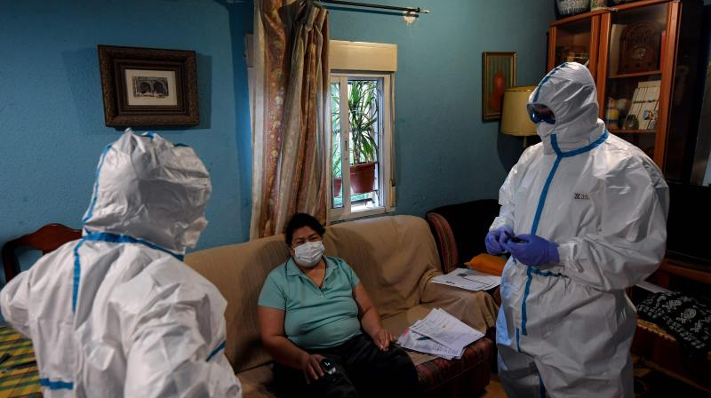 A healthcare worker of the Medical Emergency Services of Madrid (SUMMA 112) UVI-6 unit, wearing a protective suit, visits a suspected COVID-19 patient at her home in Madrid. AFP Photo