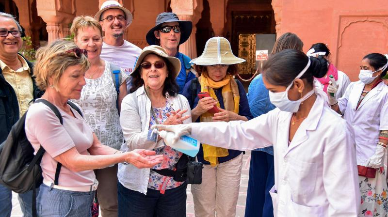A medic official pumps sanitizer on the hands of tourists to mitigate the spread of coronavirus, at Junagarh Fort in Bikaner. PTI
