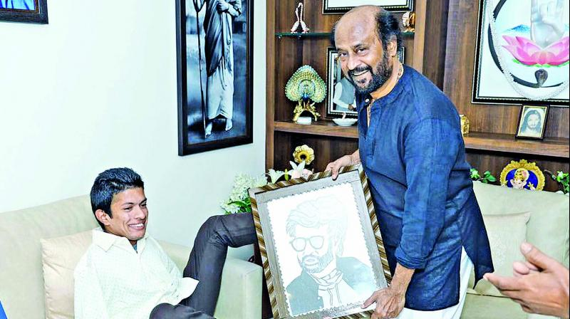 Pranav Balasubrahmanyan presents his portrait to the superstar.