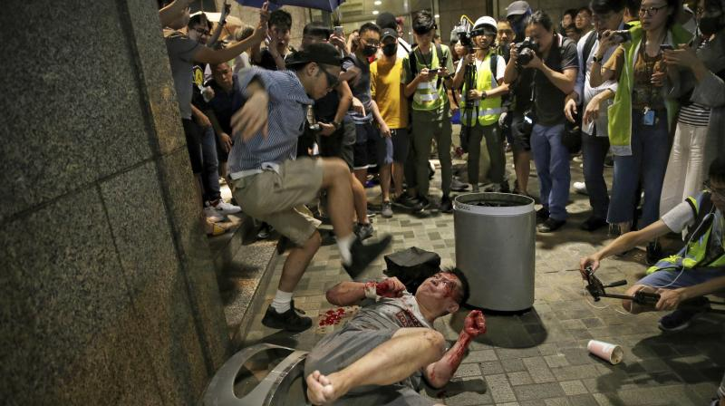 Several people were wounded, with one man in a white tee-shirt, believed to be the knifeman, being beaten with sticks by protesters. Another man lay in a pool of blood on the pavement outside the mall. (Photo: AP)