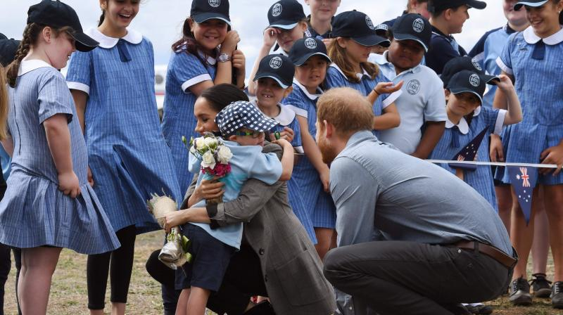 Britain's Prince Harry (R) looks on as his wife Meghan, the Duchess of Sussex is hugged by student Luke Vincent of Buninyong Public School following the couple's arrival at Dubbo Regional Airport in Dubbo on October 17, 2018. (Photo: AFP)