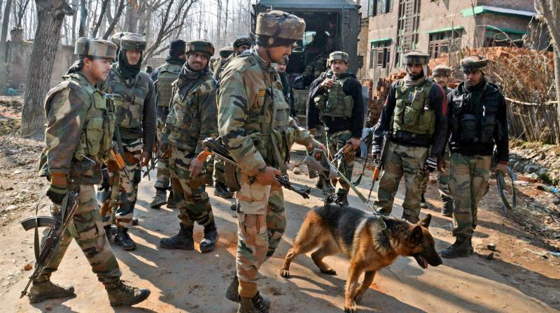Army personnel along with a sniper dog move towards the house where militants were hiding during an encounter at Frisal area of Kulgam district of south Kashmir. (Photo: PTI)
