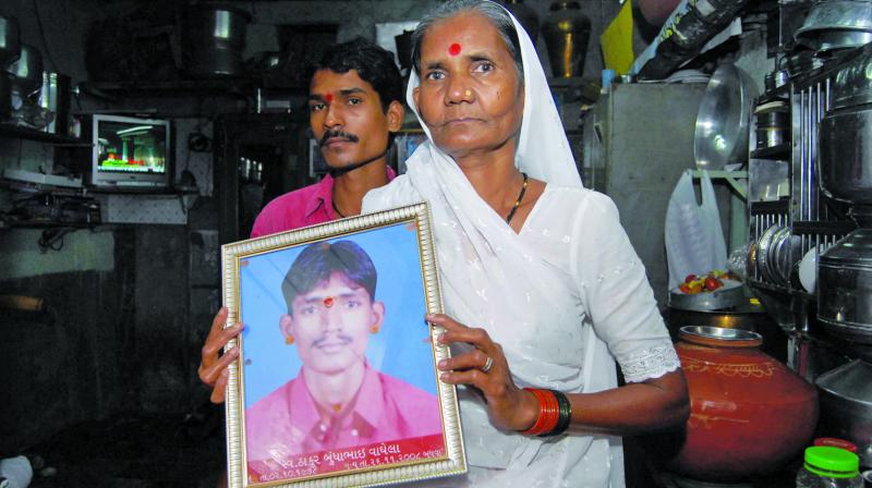 Thakur Waghela's mother holds up a portrait of his.