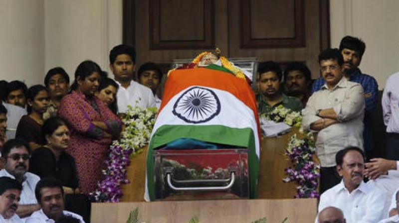Politicians and friends surround the body of Jayalalithaa, who was dressed in green for her final journey. (Photo: PTI)