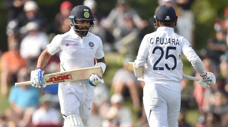 India's captain Virat Kohli and Cheteshwar Pujara run between the wickets on day two of the second Test cricket match between New Zealand and India at the Hagley Oval in Christchurch. AFP