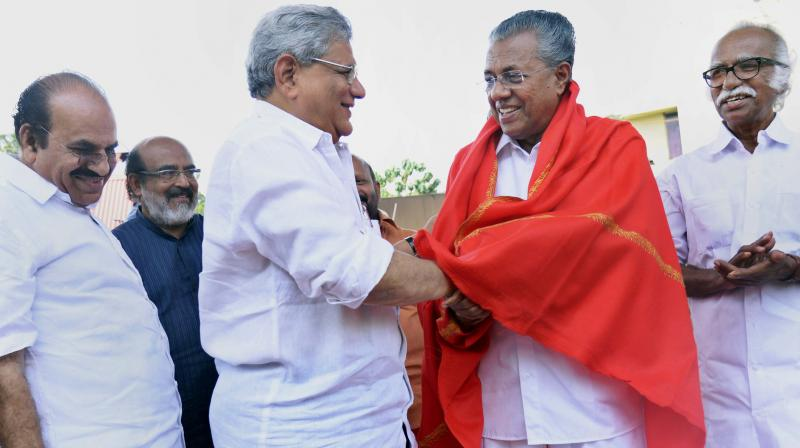 CPI(M) General Secretary Sitaram Yechury giving a red shawl to Kerala Chief Minister Pinarayi Vijayan at a dharna in front of the Reserve Bank of India office in Thiruvananthapuram on Friday. (Photo: PTI)