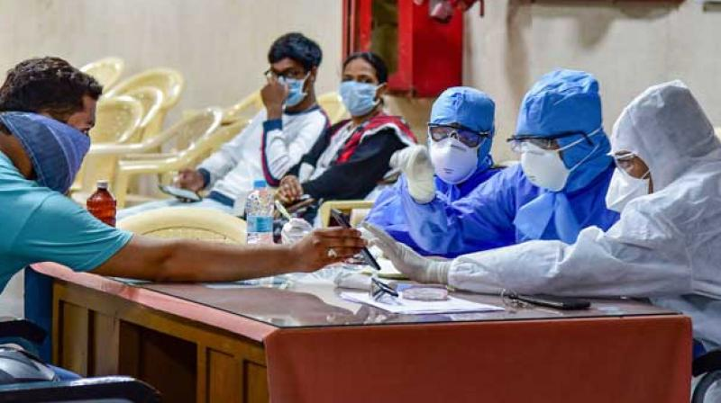 Medics interact with a patient at a help desk set up in view of the coronavirus pandemic at the Gandhi Hospital in Hyderabad (PTI)