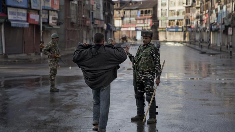 In this Aug. 8, 2019 file photo, an Indian paramilitary soldier orders a Kashmiri to lift his robe before frisking him during curfew in Srinagar. AP Photo