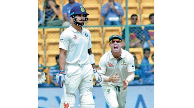 David Warner celebrates as India captain Virat Kohli looks stunned after being trapped by Nathan Lyon.