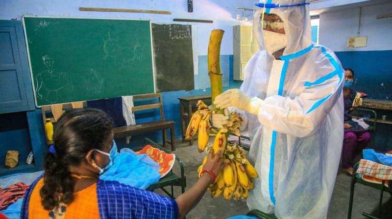 A medic wearing PPE suit distributes bananas to a teacher in Delhi. — PTI photo