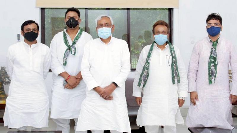 Bihar CM Nitish Kumar poses with newly joined members of JD(U) in Patna. — PTI photo