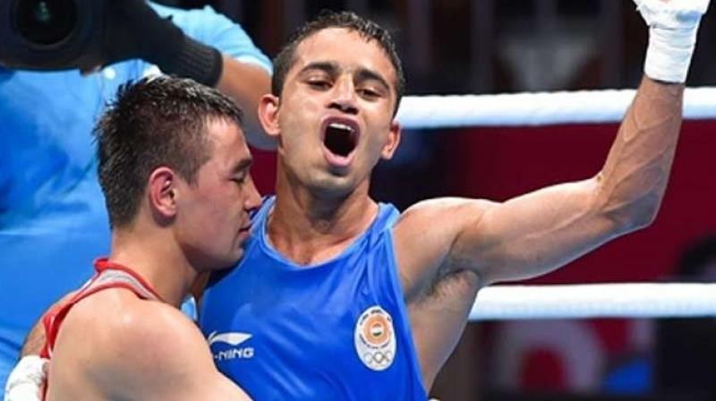 Amit Panghal (in blue) celebrates after defeating reigning Olympic and Asian champion Hasanboy Dusmatov of Uzbekistan in their men's light fly (46-49kg) division boxing final in Jakarta on Saturday. Amit won by a 3-2 verdict. (Photo: PTI)