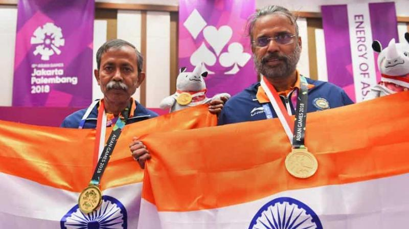 Gold medallist Pranab Bardhan and Shibhnath Sarkar pose with the Indian tricolour after winning in the bridge competition at the 18th Asian Games in Jakarta. (Photo: PTI)