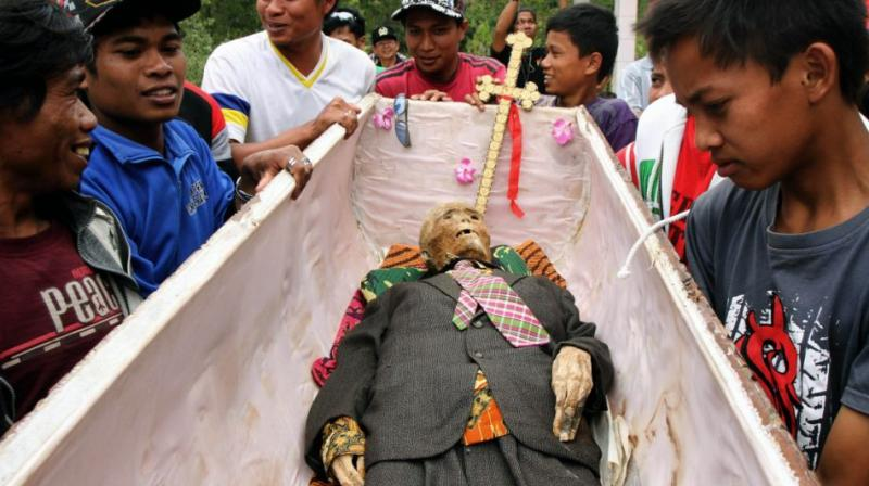 """The scene is part of an ancient Torajan ritual known as """"Ma'nene"""", in which clans visit the tombs of deceased family members. (Photo: AP)"""