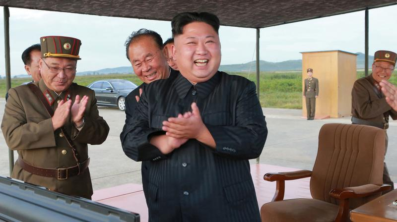 North Korean leader Kim Jong Un, center, celebrates what was said to be the test launch of an intermediate range Hwasong-12 missile at an undisclosed location in North Korea. (Photo: AP)