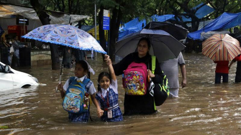 School children wade through a waterlogged street following heavy rains in Mumbai. (Photo: AP)
