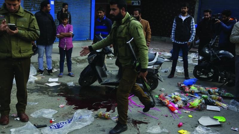 A policeman walks past a pool of blood at the spot of a grenade explosion at a market in Srinagar on Monday. (Photo: AP)