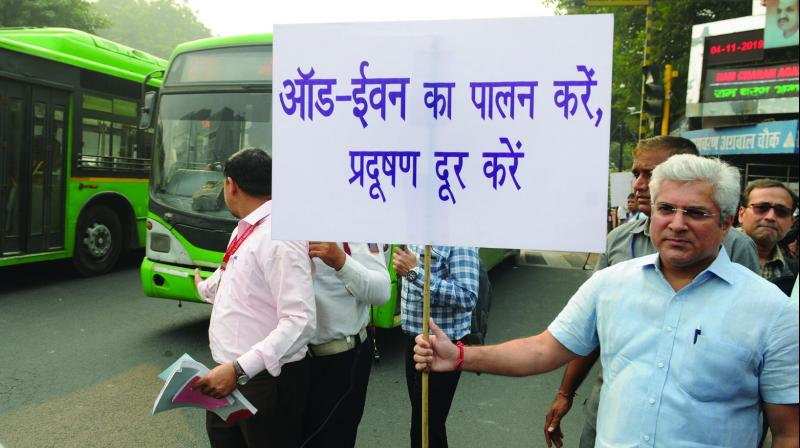 Transport minister Kailash Gahlot displays a placard asking people to obey the  odd-even rule at ITO in New Delhi on Monday. (Photo: Biplab Banerjee)