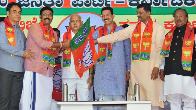 Karnataka chief minister B.S. Yediyurappa, BJP state unit president Nalin Kumar Kateel and BJP national general secretary Muralidhar Rao hand over the party flag to MLA Anand Singh during a programme to induct the disqualified MLAs in Bengaluru. (Photo: PTI)